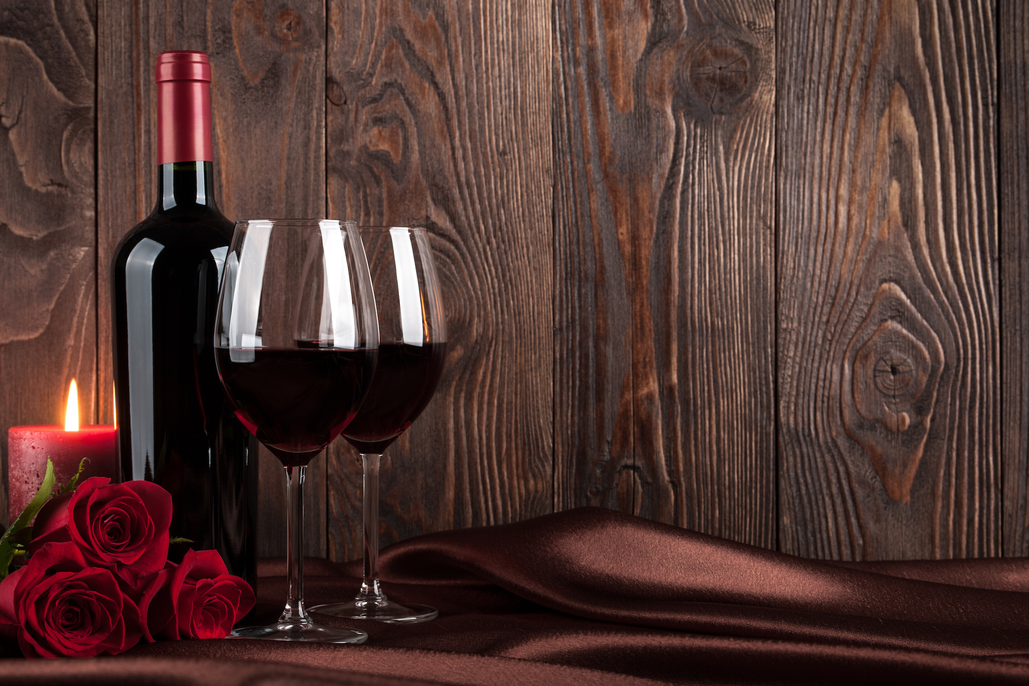 Red wine bottle, two glasses of wine, candle and red roses on brown silk